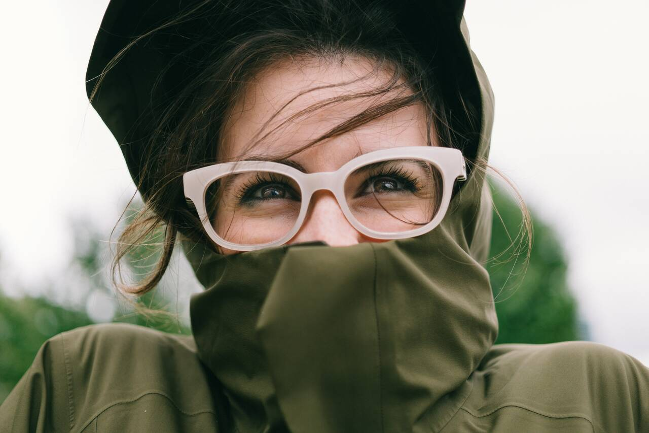 woman covering mouth with green turtleneck top - Optiker Löw